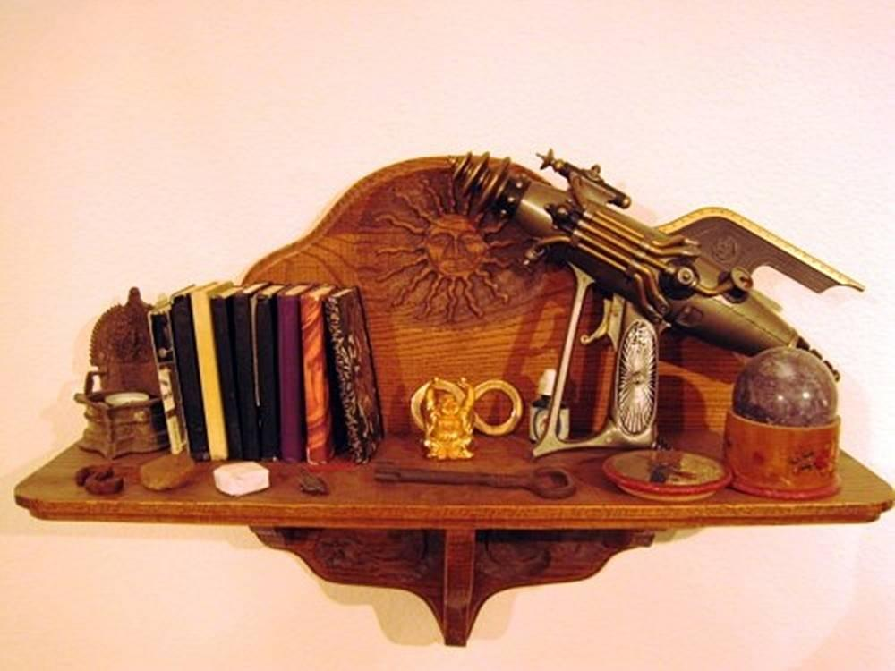 A small, ornately carved wooden shelf holding a Voice Blaster, several stones, a golden lemniscate, the take back your balls statue, several other small things as well as multiple Beep! Books
