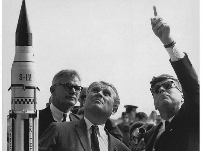 NASA Dr. Wernher von Braun (center) describes the Saturn Launch System to President John F. Kennedy (right, pointing). NASA Deputy Administrator Robert Seamans stands to the left of von Braun.