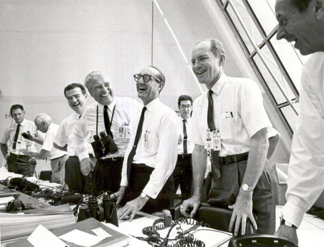 NASA Apollo 11 mission officials relax in the Launch Control Center following the successful Apollo 11 liftoff on July 16, 1969. Second from left (with binoculars) stands Dr. Wernher von Braun, Director of the Marshall Space Flight Center.