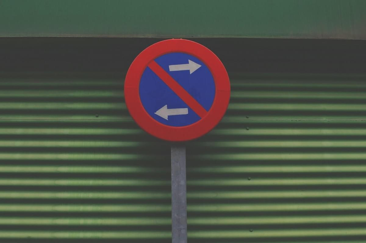 "A photo of a round street sign showing one arrow going left and one arrow going right, as shown in the ""What, Me Worry?"" blog post from The Purple Dog Vegan"
