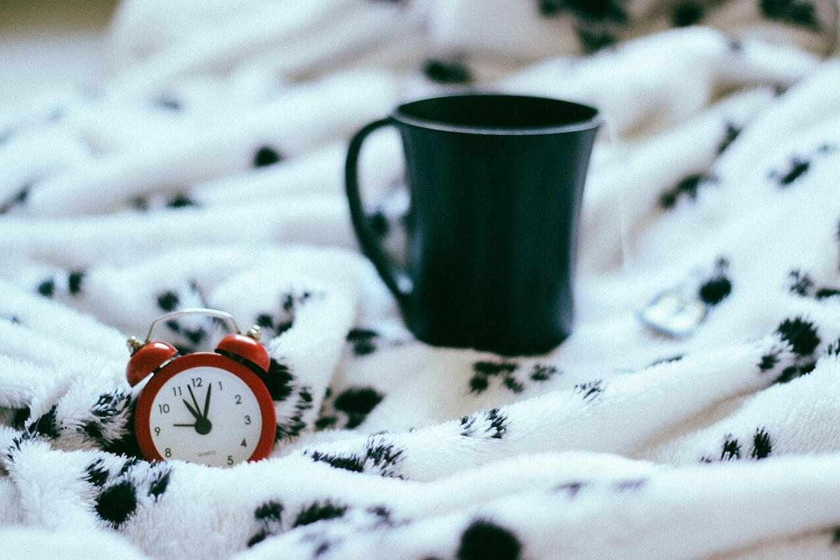 "A photo of a coffee cup and an alarm clock on a blanket on a bed as featured in The Purple Dog Blog post ""* Simple Rules for Better Mornings"" by The Purple Dog Vegan"