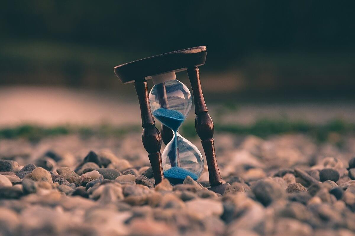 "A photo of an hourglass filled with blue sand, tilted and sitting on a rocky ground as featured in ""Time Management is a Mythical Creature,"" a Purple Dog Blog post by The Purple Dog Vegan"