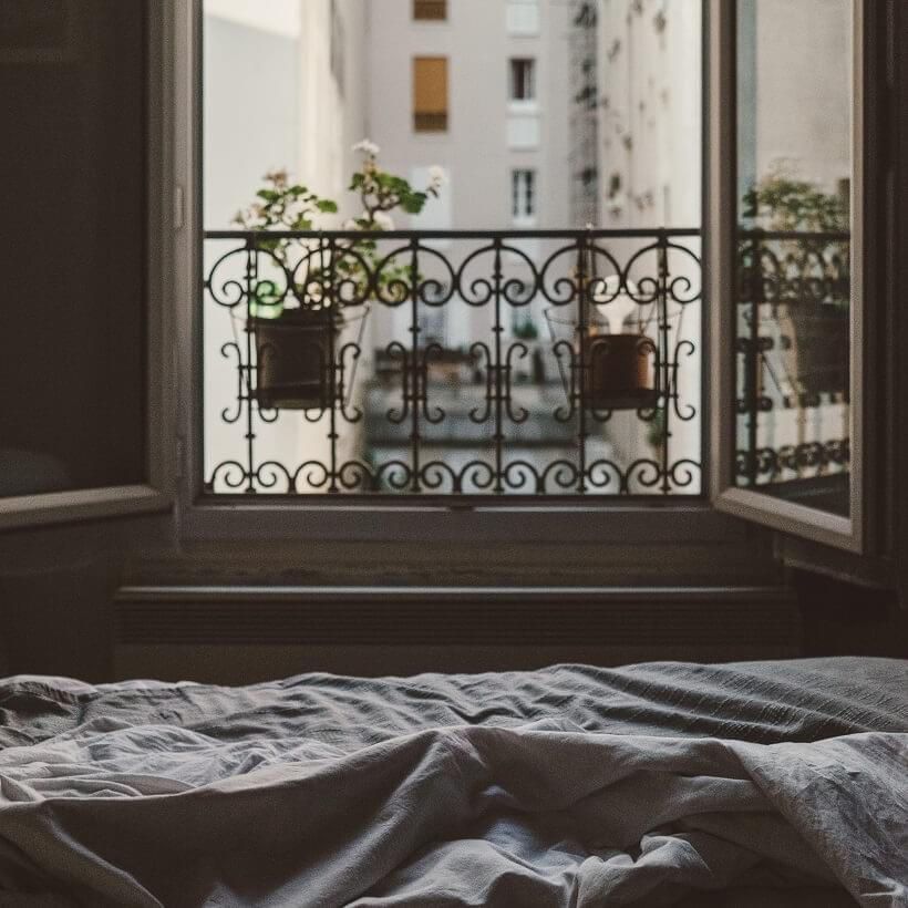 "A photo of the view from a bed looking out of an open window as featured in The Purple Dog Blog post ""* Simple Rules for Better Mornings"" by The Purple Dog Vegan"