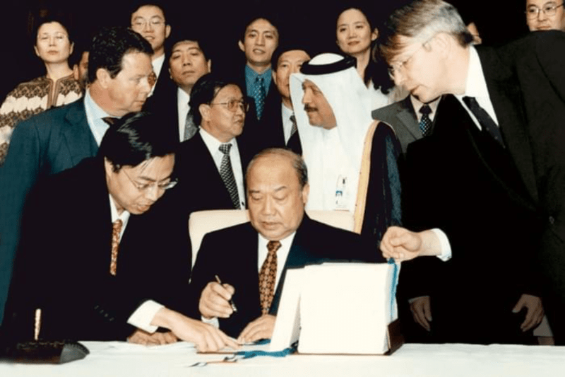 Shi Guangshen, Minister of Foreign Trade and Economic Cooperation of China, signing China's ascension to the WTO in November 2001. Photo courtesy of the WTO.