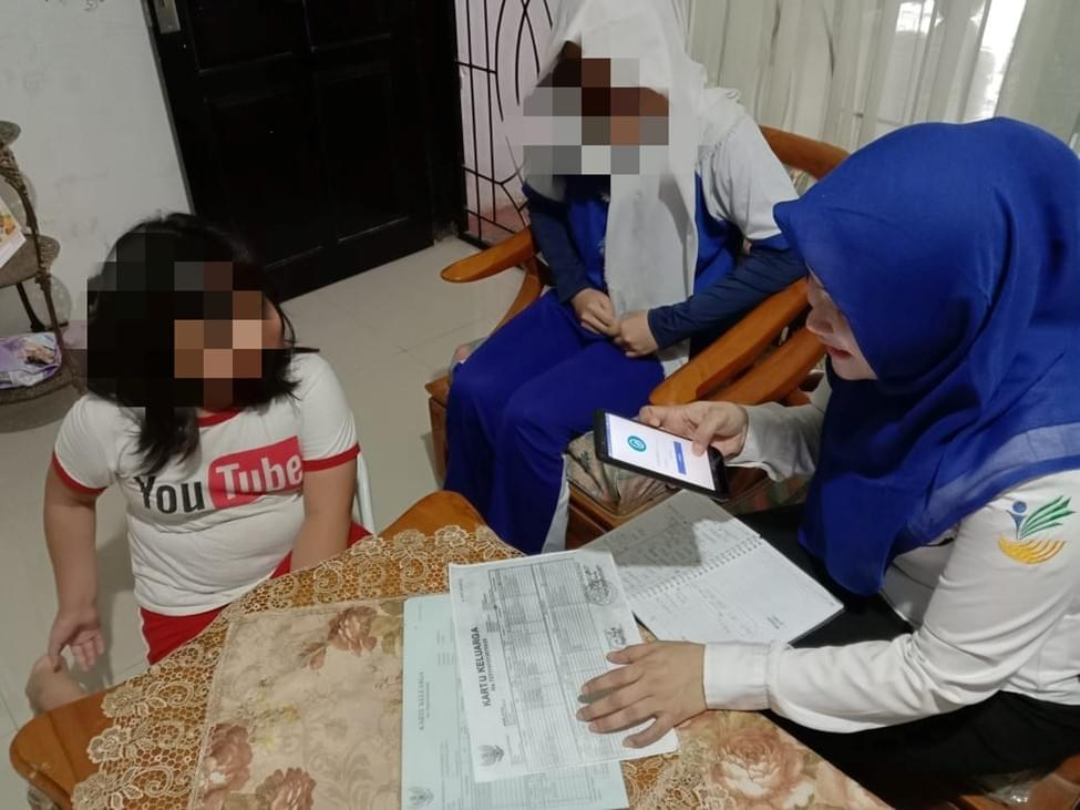 Ibu Soraya meeting with one of her charges. She is using the Primero app to complete the profile of the child and verifies that the official documents are in order. ©UNICEF/2020
