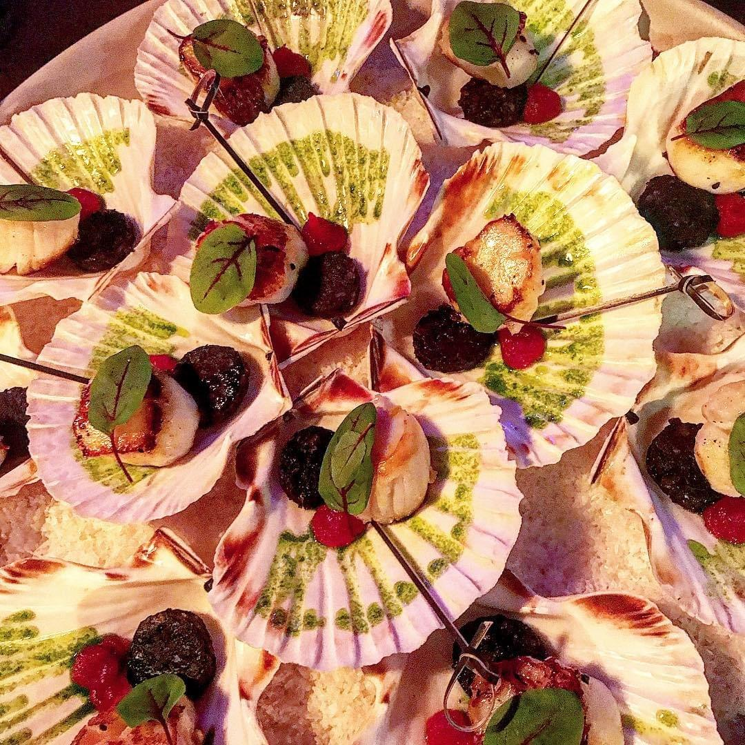 Image of Scallop, Black Pudding, Blood Orange Gel Canape, served in the shell for a Leeds corporate event