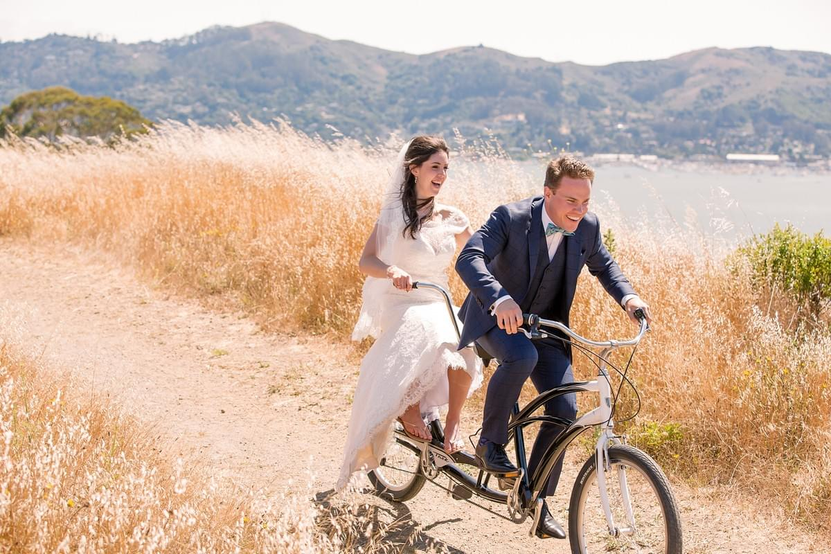 Wedding couple biking down a field by the water.