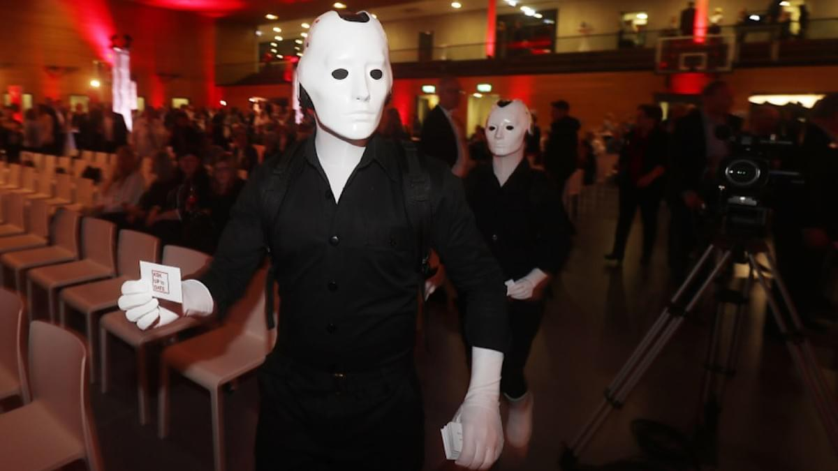 Silent Rocco's Menschine robot act handing out flyers at a corporate event