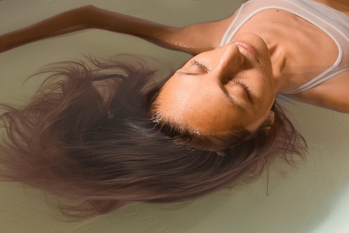 A woman leans back and allows her arms to drift above her head as she rests peacefully in a sensory deprivation tank at Float Carolina.