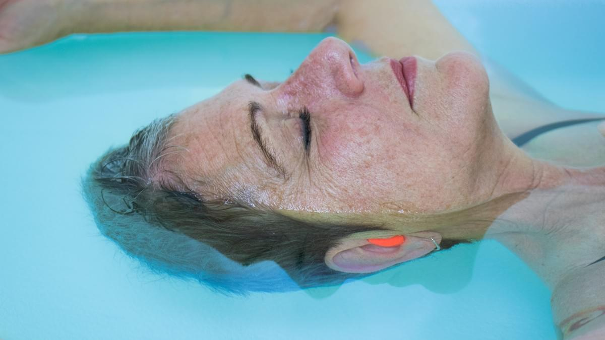 An older woman is at peace, floating effortlessly in a tank at Float Carolina.
