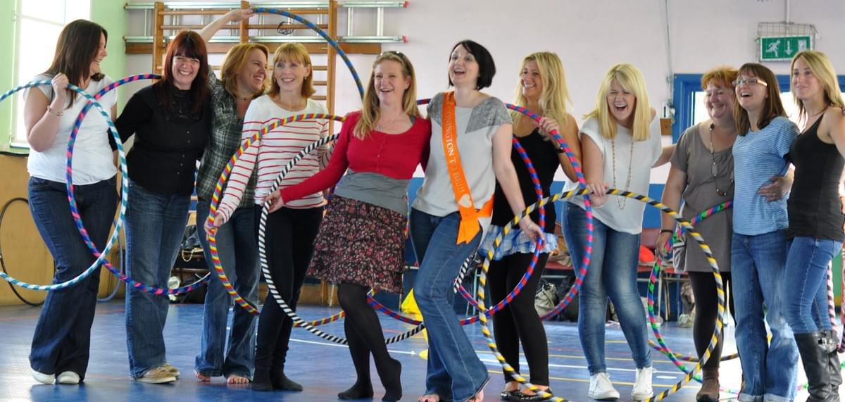 Smiling hula hooping hen party.