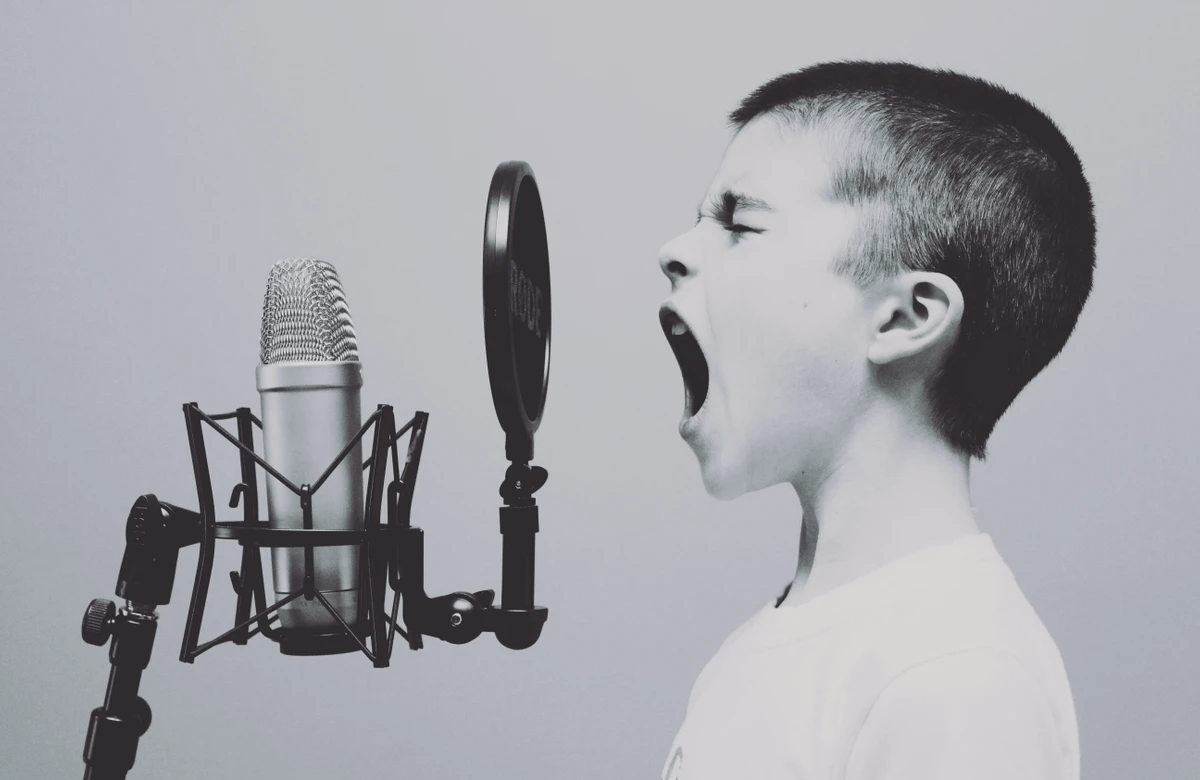 A boy trying to promote his podcast by shouting into an unplugged microphone