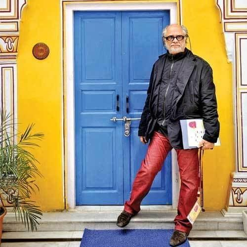 A portrait of Homi Bhabha in front of a blue door, yellow wall, wearing red pants and black jacket and holding some paperwork and a lanyard. Source unknown.