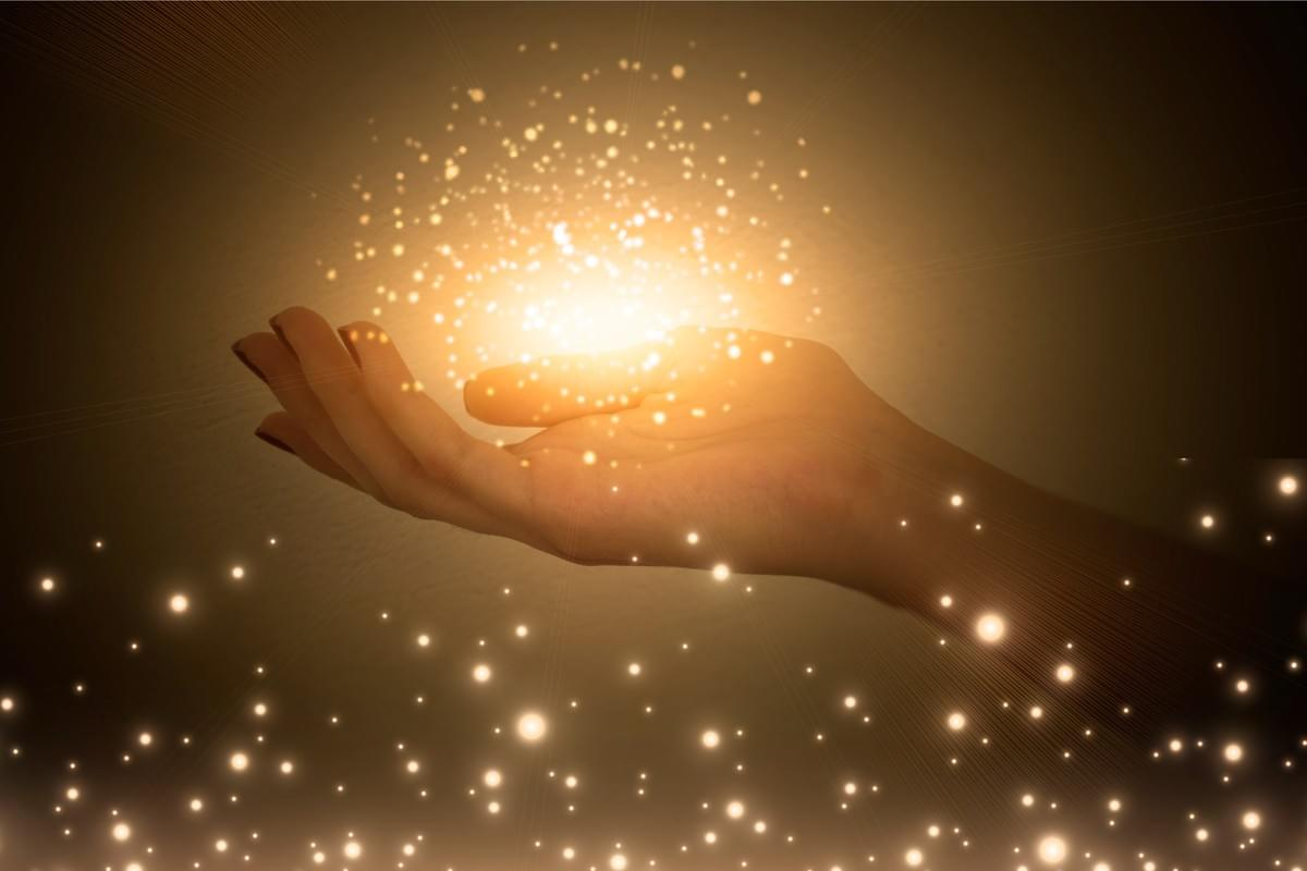 outstretched hand with ball of sparkle and light above
