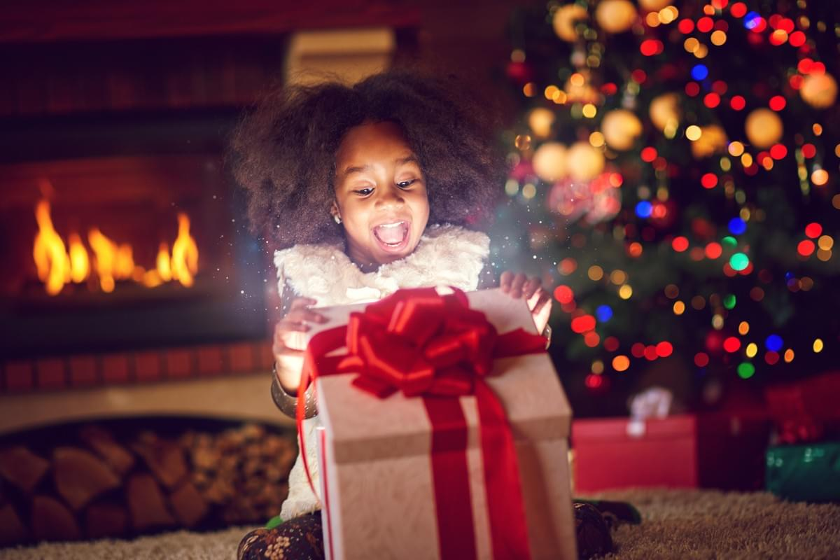 a young girl excitedly opening her present in front of a christmas tree