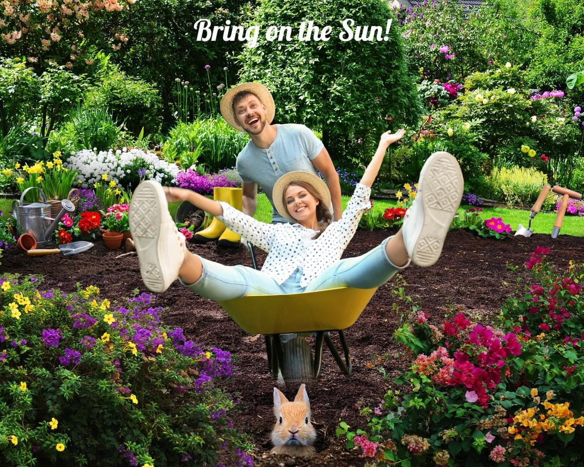 Couple in a garden with a man pushing his significant other in a wheelbarrow while she has her arms and feet up in the air