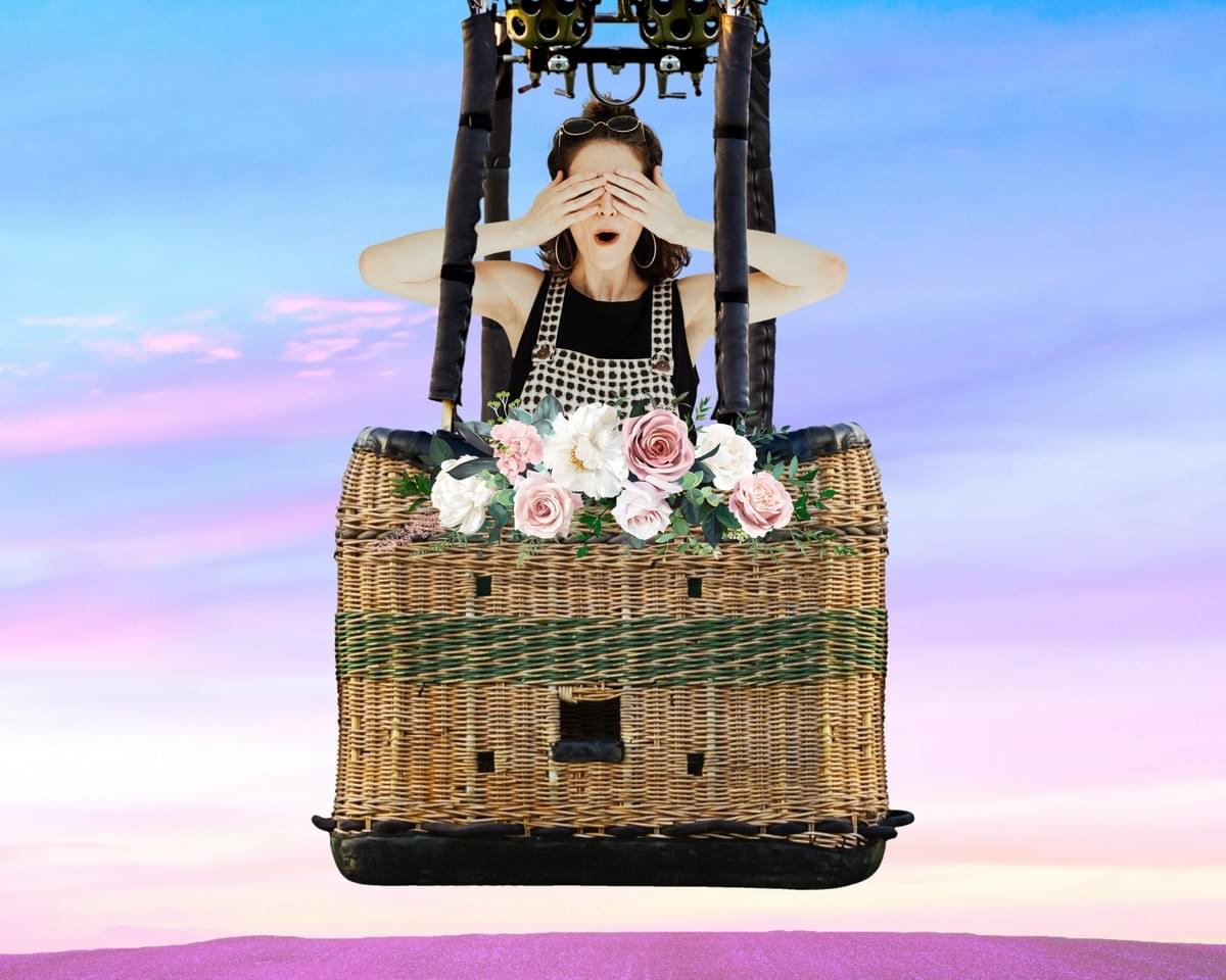 woman is in a hot air balloon wicker basket covering her eyes with her hands, and the blue and purple sky is behind her