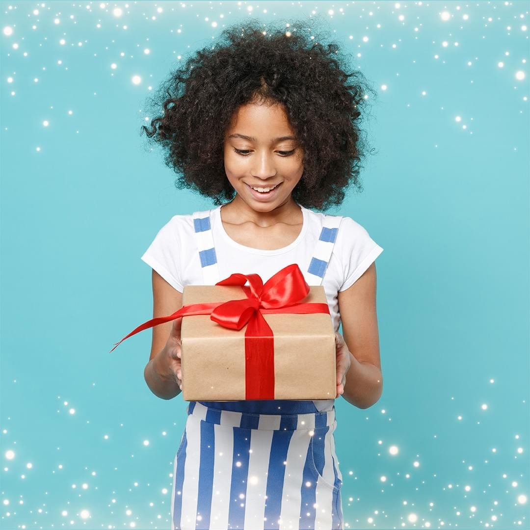 girl excitedly looking at a wrapped present