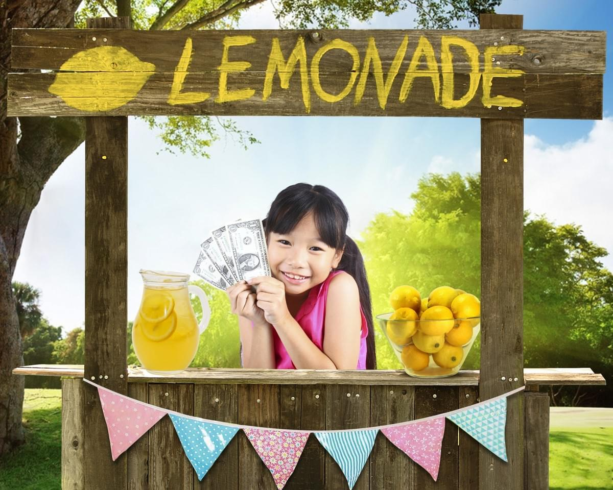 young girl is standing behind a lemonade stand with her hands up holding dollar bills, it is a sunny spring day