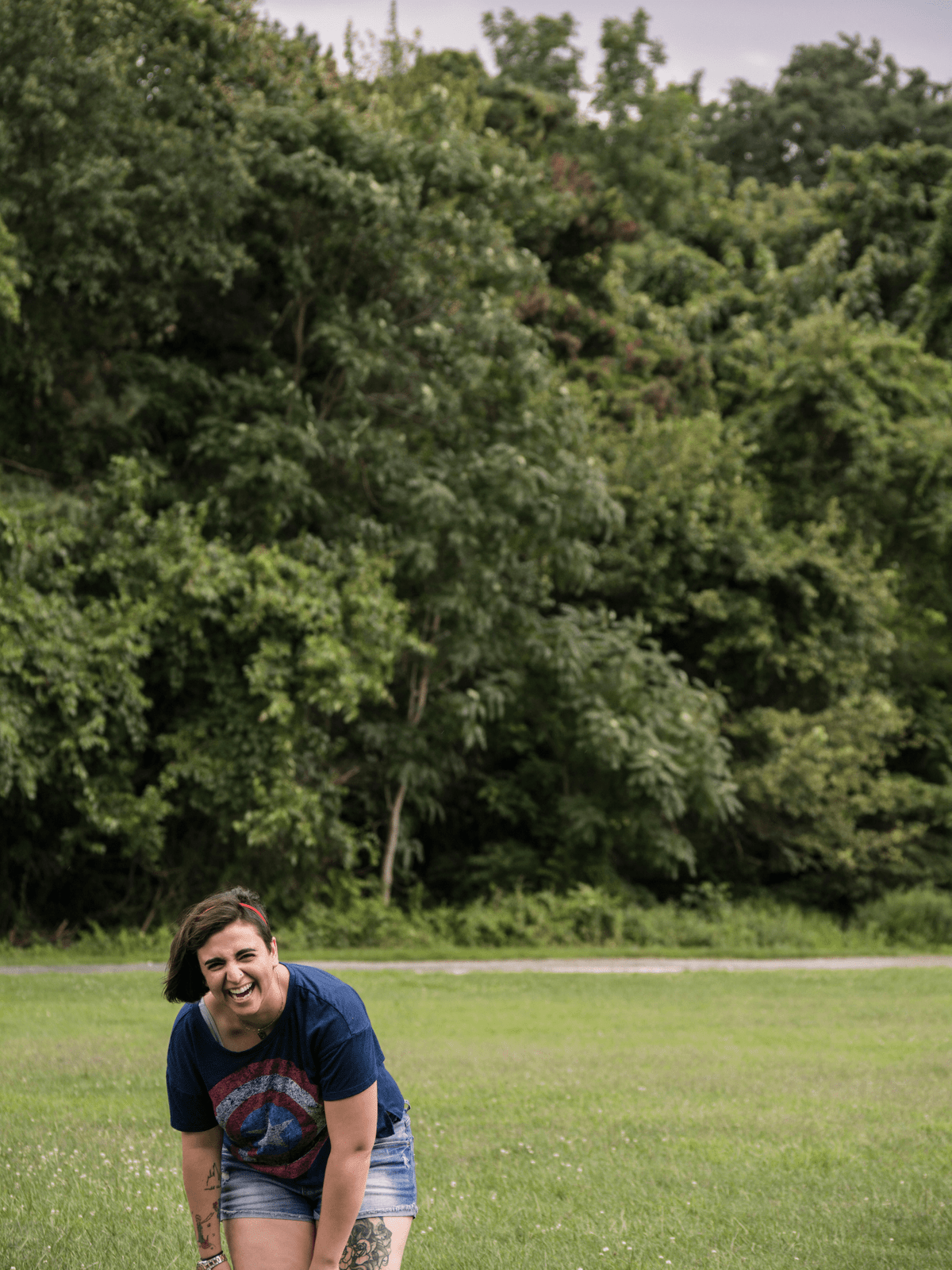 An image of Naseem, a nonbinary brown-haired person wearing a blue Captain America shirt, red headband, and jean shorts. They are laughing, bent over, and on a stretch of grass with trees behind them.