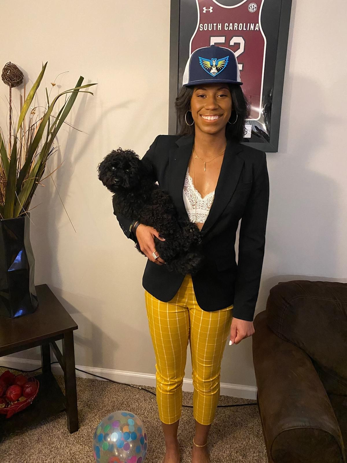 Photo of Ty on draft night wearing Wings hat, black blazer over white lace bralette and yellow checkered pants. She holds a small fluffy black dog (Gucci) in one arm.