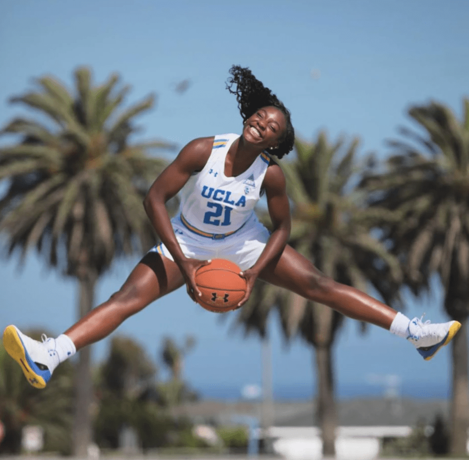 Michaela jumps into splits in UCLA jersey with palm trees in the background