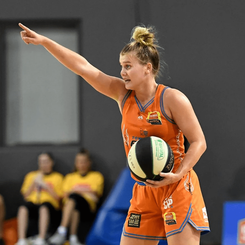 Shyla points while holding the ball in an orange uniform