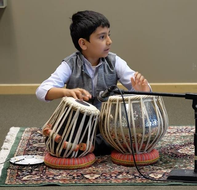 Young kid playing the tabla.