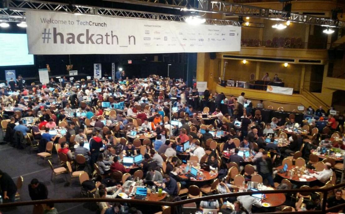 Image of startup developers and tables in a large conference area at TechCrunch hackathon.