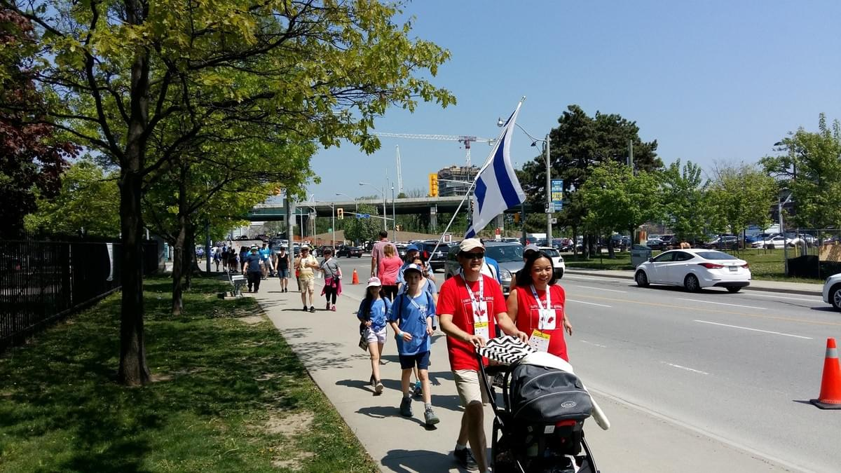 Walkekrs pass by the Israel Truth Week 'Jews are owners!' cheerleading station near the end of the Walk With Israel, Toronto, May 27/18.