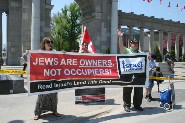 BANNER: 'JEWS ARE OWNERS, NOT OCCUPIERS!' Mark Vandermaas (R) and Joyce Aldrich (L) hold banner and wave to participants of the Walk With Israel near the Canadian National Exhibition in,Toronto.