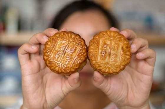 Image showing man holding up mooncakes with Chinese characters imprinted