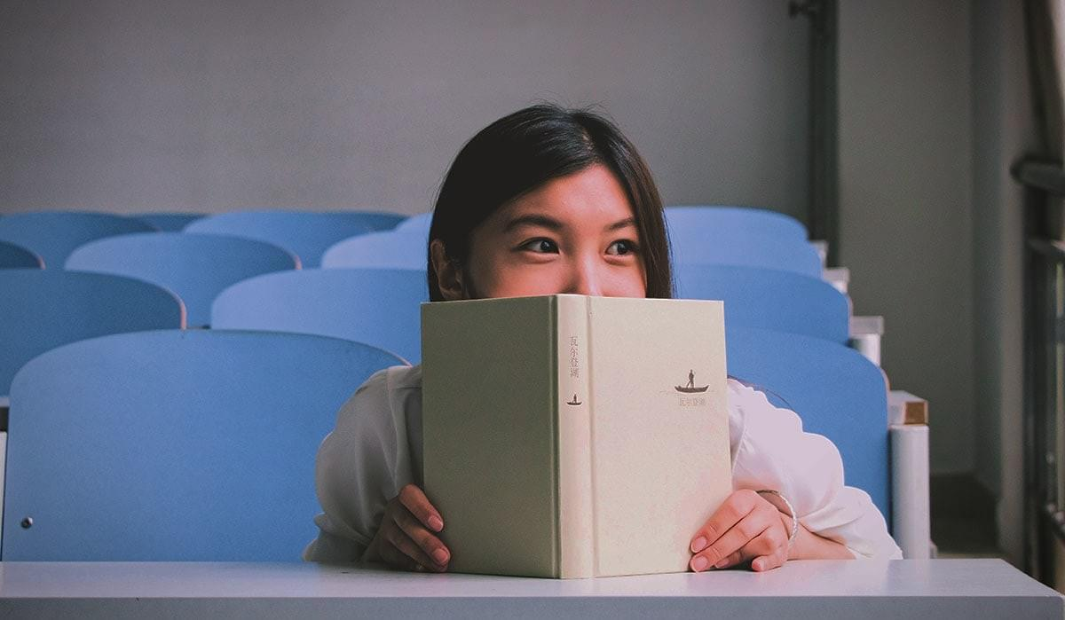 Image showing a young girl reading a Mandarin Chinese book in a classroom.