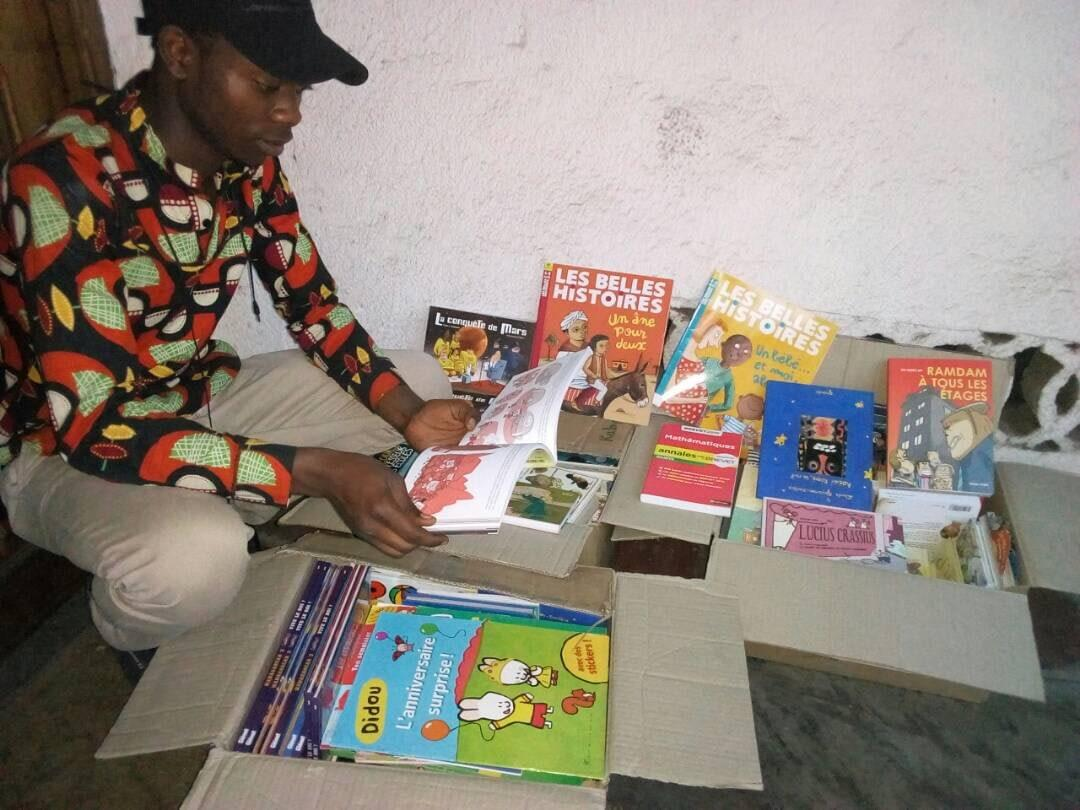 A youth at SKV Youth Center in Katoyi unpacks the three cartons of kids books they received today.