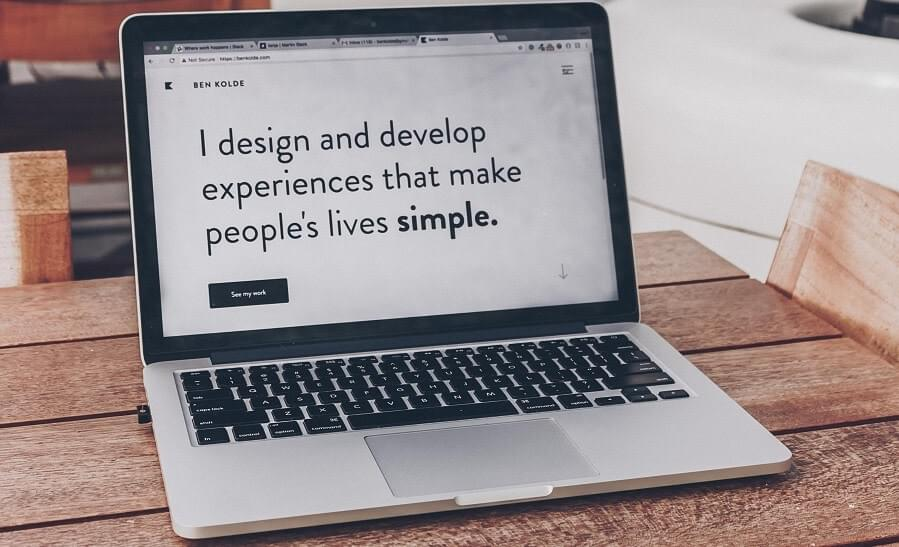 "A computer showing on screen logo that reads: ""I design and develop experiences that make people's lives simple."""