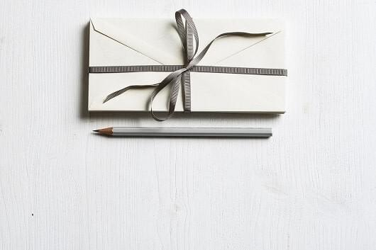 Wrapped gift and a silver pencil.
