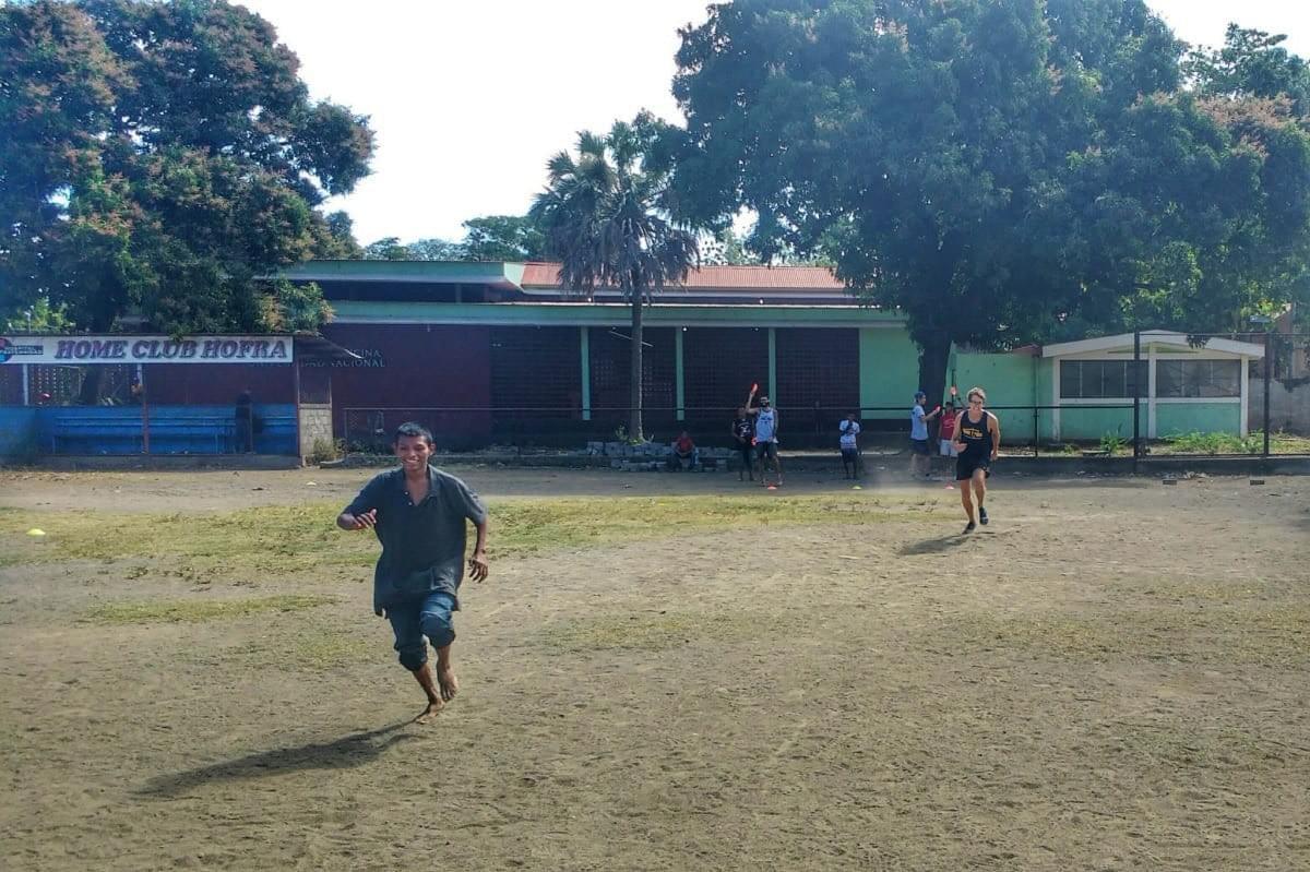 Local teenagers taking part in running relays during a Quetzaltrekekrs sport session on a baseball field in León, Nicaragua