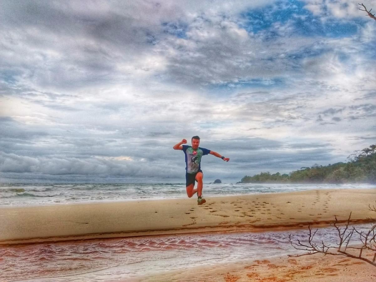 Jumping over a creek on Wizard Beach, Bastimentos Island, Panama