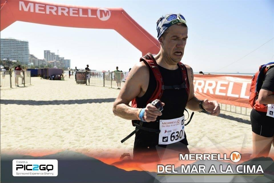 A runner crosses the finish line at Del Mar a La Cima ultra marathon, a pained look on his face