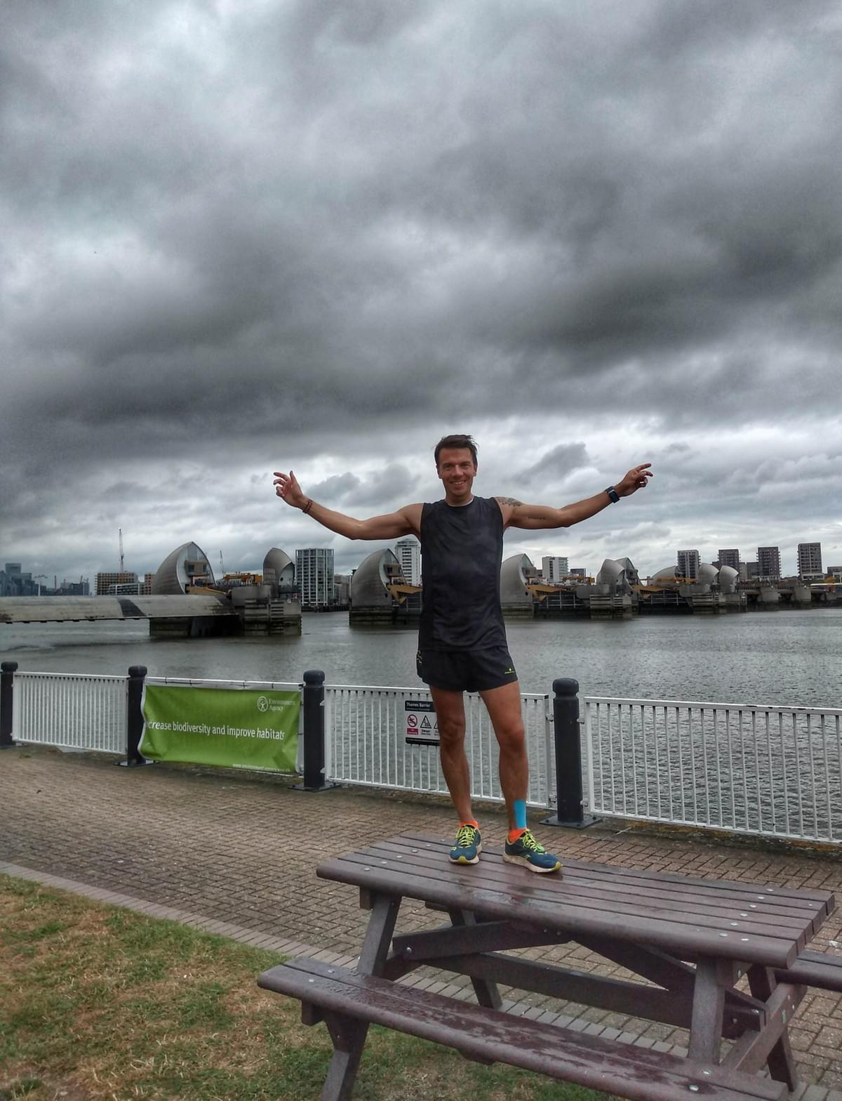 Runner poses for a celebration photo in front of the Thames Barrier, conclusion of the Thames Path