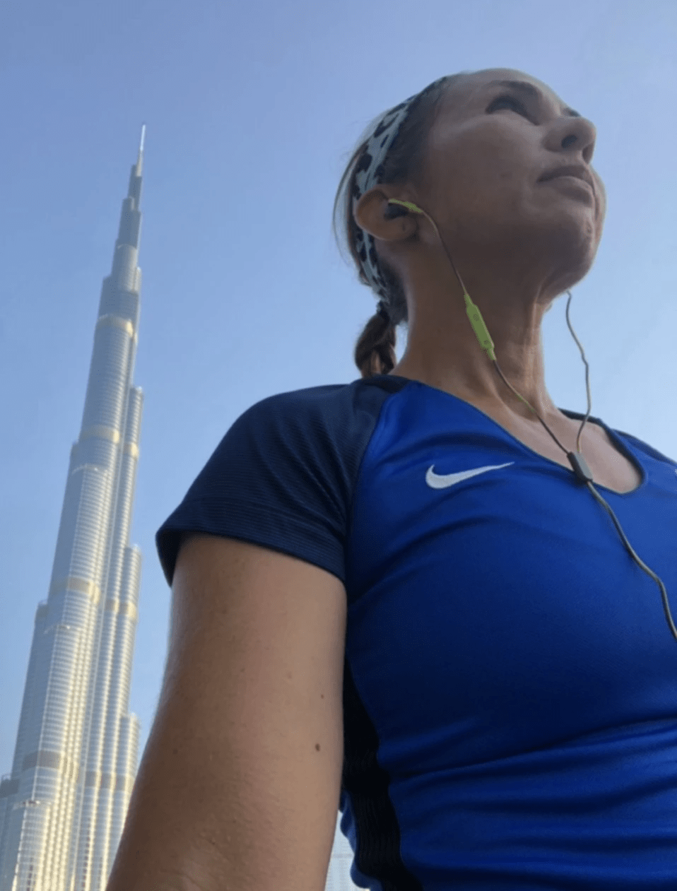 female runner poses in front of burj khalifa dubai UAE