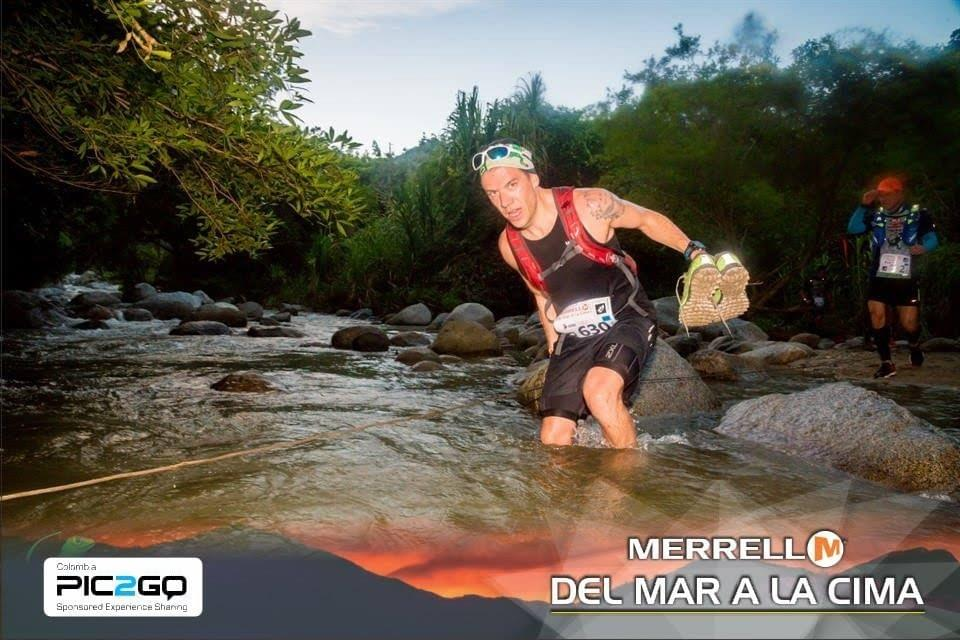 A runner holds his shoes as he makes a river crossing at Del Mar a La Cima ultra marathon