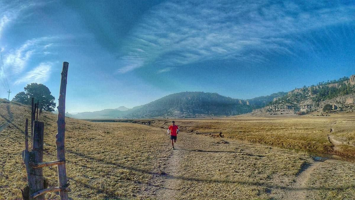 A trail runner following a narrow track through plains in the Sierra Tarahamura. Mexico