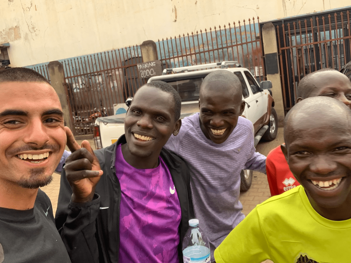 a group of ugandan elite athletes and coaching staff laugh during a photo