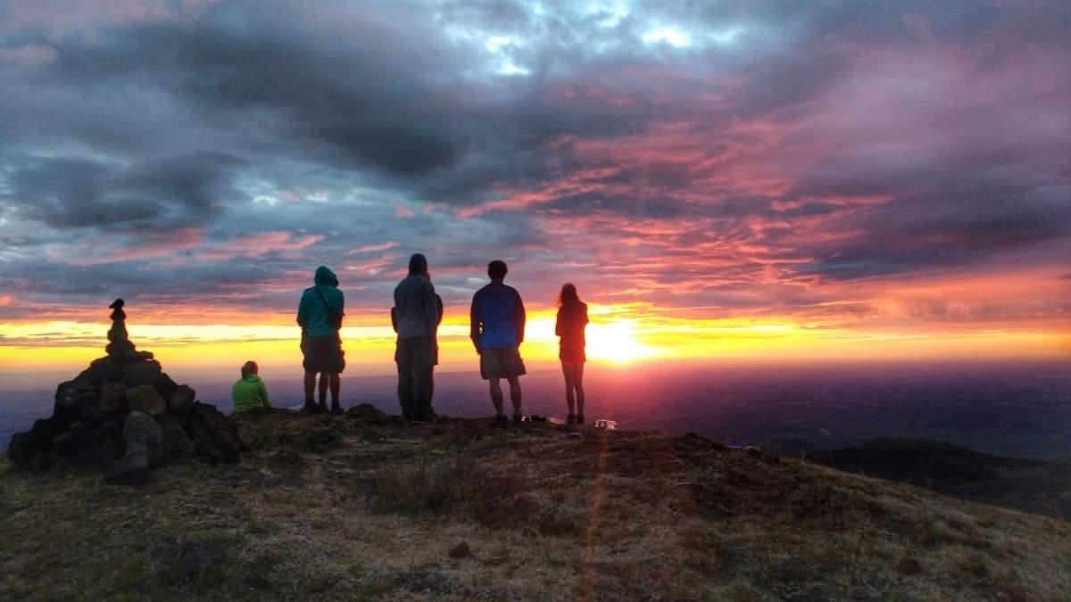 A group of Queztaltrekkers hikers view a spectacular sunset from the top of a volcano