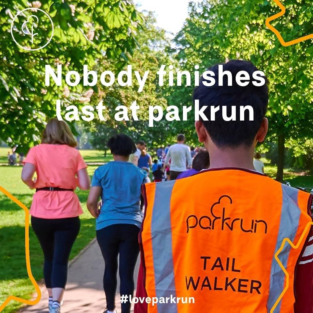 A parkun tail walker on a course behind two female parkrun participants
