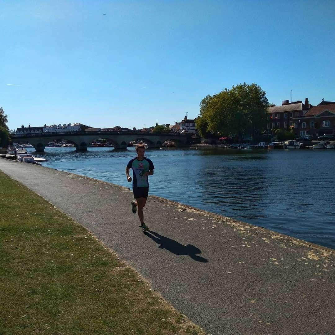 Man running on the Thames Path alongside the river in Henley-on-Thames