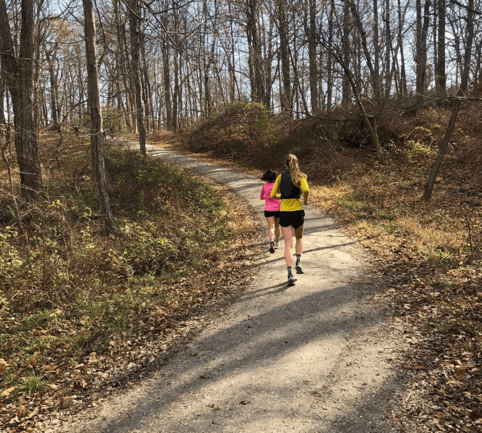 Two female New York runners running a woodland trail in a New York park