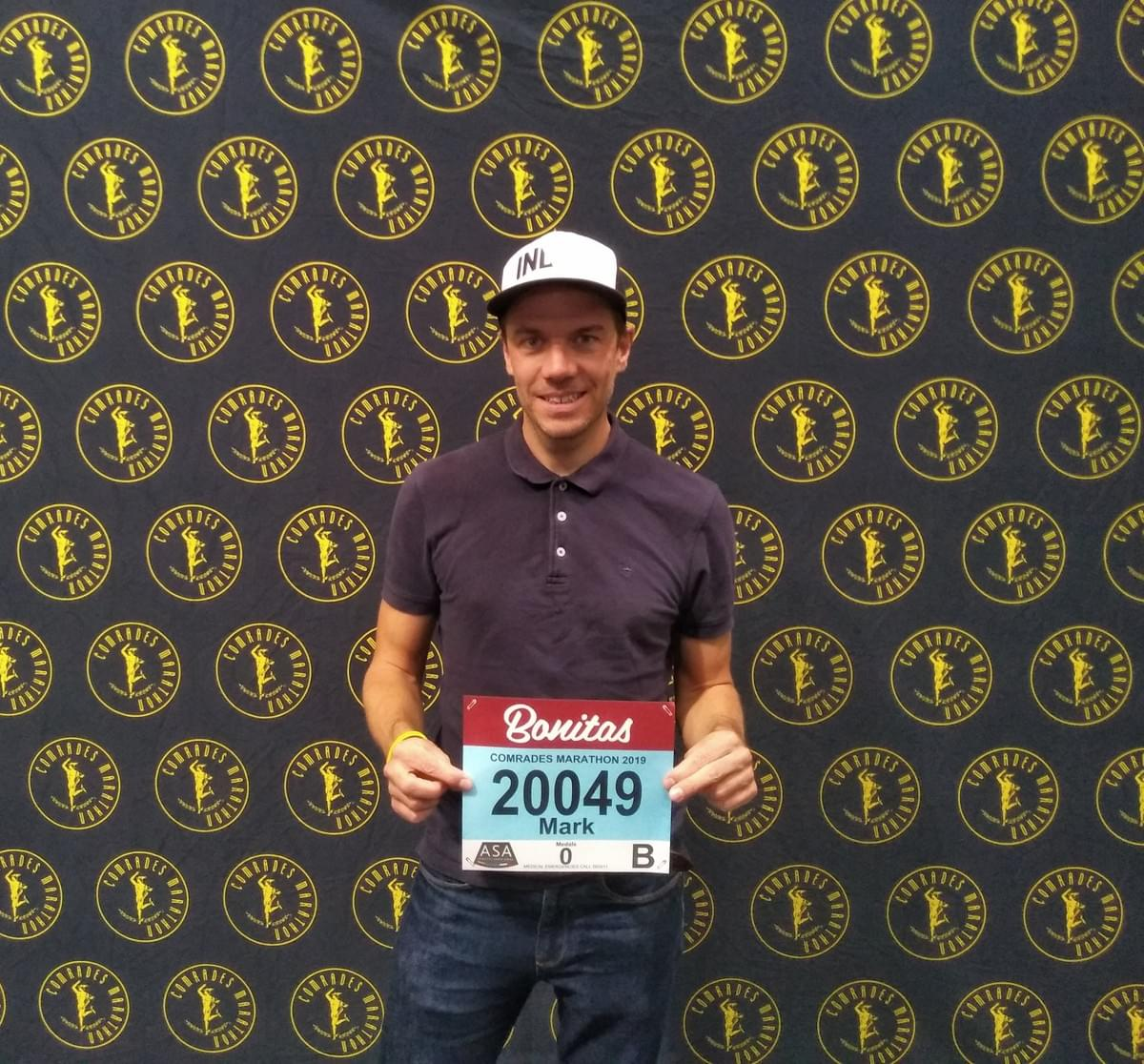 Ultra runner holding his race number at the 2019 Comrades Marathon expo in Durban