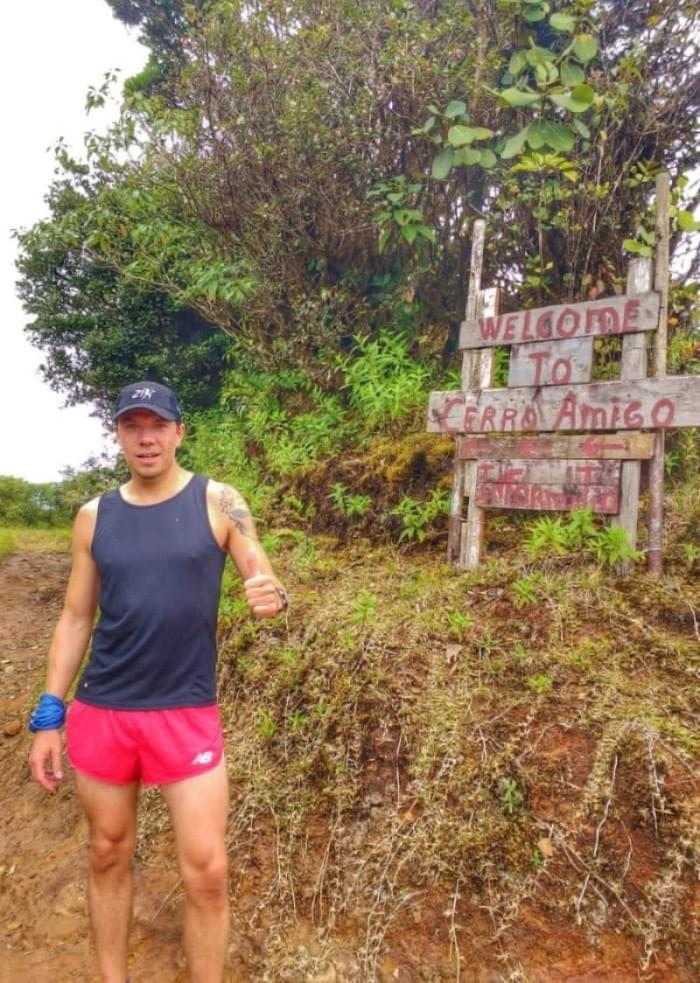 Standing by the sign at the top of Cerro Amigo, Monteverde